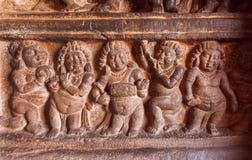 Exempel av indiska konstcarvings med danspartiet av forntida folk på väggen av 6th århundradetempel i Badami, Indien Arkivbild