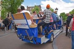 Exempel av particykeln i Amsterdam med passagerare som har mycket gyckel tillsammans Royaltyfri Fotografi