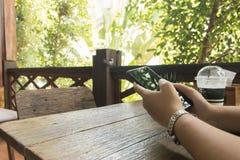 Exemplaarruimte van de celtelefoon van de handgreep op houten lijst met aard Royalty-vrije Stock Fotografie