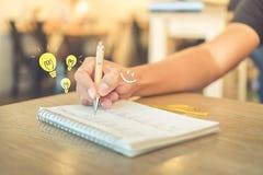 Exemplaarruimte van vrouwenhand die in wit notitieboekje neerschrijven stock foto's