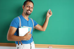Exemplary student standing near blackboard with books and chalk. Royalty Free Stock Photo