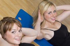 Exercício aeróbio da mulher dois nova em uma ginástica imagens de stock