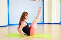 Exercício anca do exercício da torção da mulher de Pilates no gym fotos de stock