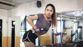 Exercício asiático da mulher com pesos no gym video estoque