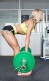 Exercício ativo da menina do esporte em sua parte traseira que levanta pesos pesados instrutores Pele brilhante Ostenta a nutriçã fotos de stock