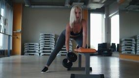 Exercício atrativo da jovem mulher com os pesos que inclinam seu joelho em um banco no gym vazio com espelhos Front View filme