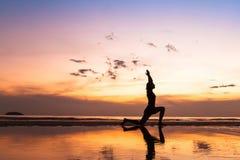 Exercício bonito da ioga na praia no por do sol imagens de stock