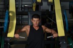 Exercício bronzeado do atleta na máquina do exercício Fotos de Stock Royalty Free