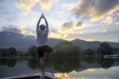 Exercício calmo da ioga das mulheres na frente da lagoa Fotos de Stock Royalty Free