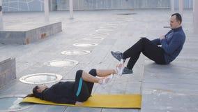 Exercício com instrutor pessoal fora A mulher encontra-se na esteira amarela que faz o ciclismo do ar O treinador que demonstra o filme