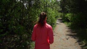 Exercício da aptidão fora Mulher do esporte que corre através das madeiras Ela ` s em um bom humor e em uma grande figura deciduo vídeos de arquivo