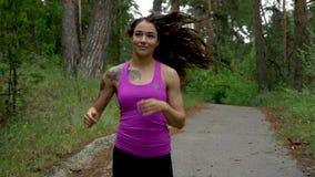 Exercício da aptidão fora Mulher do esporte que corre através das madeiras Movimento lento filme