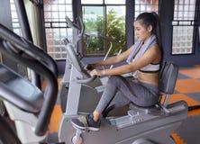 Exercício da bicicleta de exercício da moça cardio- no gym da aptidão fotografia de stock