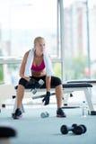 Exercício da jovem mulher com dumbells Imagem de Stock