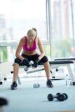 Exercício da jovem mulher com dumbells Fotografia de Stock