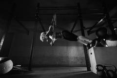 Exercício da mulher da aptidão no TRX no gym imagem de stock royalty free
