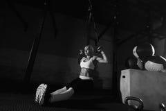 Exercício da mulher da aptidão no TRX no gym imagens de stock