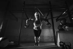 Exercício da mulher da aptidão no TRX no gym foto de stock royalty free