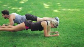 Exercício da prancha do treinamento do homem e da mulher dos pares da aptidão na grama no parque do verão video estoque