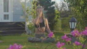 Exercício da respiração da ioga de Pranayama por uma jovem mulher no quintal de sua casa filme