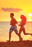 Exercício de corrida movimentando-se dos pares na praia do por do sol Fotografia de Stock