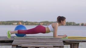 Exercício de Crossfit, mulher bonita forte da aptidão nos esportes que treina a roupa que faz o exercício da prancha na ponte na  video estoque
