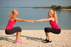 Exercício de duas mulheres na praia que faz ocupas Imagem de Stock Royalty Free