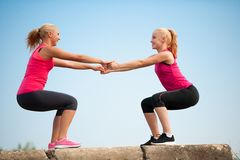 Exercício de duas mulheres na praia que faz ocupas Imagens de Stock Royalty Free