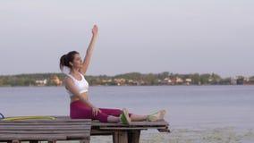 Exercício de esticão de execução fêmea da aptidão feliz com inclinações do corpo aos lados durante esportes que treinam na nature video estoque