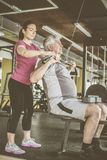 Exercício de trabalho do instrutor com o homem superior no gym Miliampère foto de stock