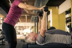 Exercício de trabalho do instrutor com o homem superior no gym Miliampère fotografia de stock