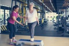 Exercício de trabalho do instrutor pessoal com a mulher superior no gym fotografia de stock