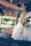 Exercício de trabalho do instrutor pessoal com a mulher superior no gym imagens de stock royalty free