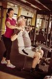 Exercício de trabalho do instrutor pessoal com o homem superior no gym foto de stock royalty free