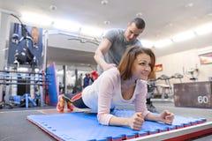 Exercício de trabalho do instrutor pessoal da aptidão com a mulher madura no gym Conceito da idade do esporte da aptidão da saúde fotos de stock royalty free