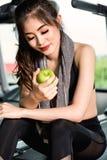 Exercício do exercício da mulher na aptidão do gym que guarda o fruto verde da maçã Foto de Stock Royalty Free