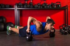 Exercício do gym da força do homem da flexão de braço de Kettlebells fotos de stock