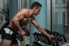 Exercício do homem novo com pesos Fotos de Stock Royalty Free
