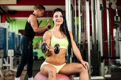 Exercício dos pares da aptidão - o homem e a mulher aptos treinam no gym imagens de stock