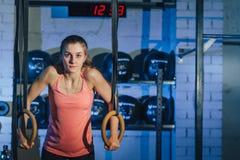Exercício em anéis do crossfit Exercício da mulher da aptidão no TRX no gym Exercício da mulher da aptidão no CrossFit Aptidão Imagem de Stock