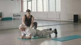 Exercício envelhecido da prancha do treinamento do homem com o treinador de esporte no clube de aptidão junto filme