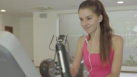 Exercício fêmea na bicicleta e escuta a música video estoque