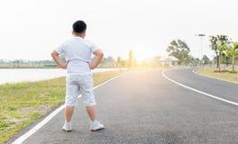Exercício gordo obeso do menino no parque na manhã imagens de stock royalty free