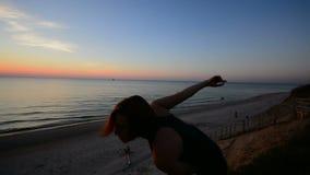 Exercício individual da mulher considerável durante o por do sol bonito vídeos de arquivo