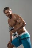 Exercício maduro do homem com pesos em Grey Background Foto de Stock Royalty Free