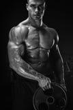 Exercício muscular do homem com placa do barbell fotografia de stock