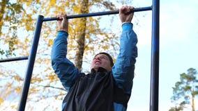 Exercício no ar fresco Indivíduo forte novo que faz exercícios na barra Parque do outono video estoque