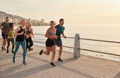 Exercício novo dos corredores ao longo de um passeio do beira-mar fotografia de stock royalty free