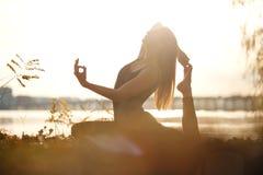Exercício praticando da ioga da jovem mulher na praia do rio e no fundo da cidade fotografia de stock
