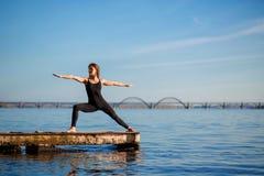 Exercício praticando da ioga da jovem mulher no cais de madeira quieto com fundo da cidade Esporte e recreação na precipitação da imagem de stock